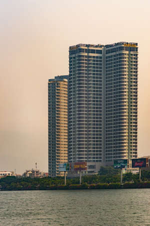 Da Nang, Vietnam - March 10, 2019: Tall VinPearl luxury hotel tower along Han River under morning sun sky. Some colorful billboards and green foliage band separating water from the rest.