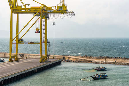 Da Nang, Vietnam - March 10, 2019: Tien Sa Port in Da Nang Bay. 2 small fishing vessels come close to dock with idle yellow container crane. Fog bank on horizon separates azure sea from blue sky. Editorial