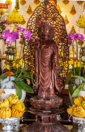 Da Nang, Vietnam - March 10, 2019: Chua An Long Chinese Buddhist Temple. Brown-maroon wooden Guan Yin statue on altar. Pink orchids and yellow fruit and flowers. Overloaded background.