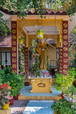 Nha Trang, Vietnam - March 11, 2019: Chua Loc Tho Buddhist temple, primary school and orphanage. Statue of Sister Thich Nu Dieu Y, founder of the orphanage under stone baldachin and green foliage. Stock Photo
