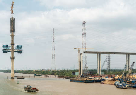 Long Tau River, Vietnam - March 12, 2019: Phuoc Khanh Bridge under construction, not yet over river, but on ramp. Tall stong pylon raises out of brown water. Under blue cloudscape, boats, barges, and