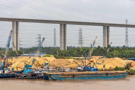 Long Tau River, Vietnam - 12. März 2019: Bau der Phuoc Khanh Hängebrücke unter silbernem Himmel, geschnitten durch viele Hochspannungskabel. Hügel aus gelbem Sand und blauen Pontos auf braunem Wasser. Grünes Laub. Standard-Bild