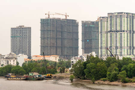Ho Chi Minh City Vietnam - March 12, 2019: Song Sai Gon river. Development and construction of tall apartment buildings behind lower housing and green foliage screen. Pontoons and crane on the water.