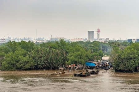 Ho Chi Minh City Vietnam - March 12, 2019: Song Sai Gon river inlet leading to slums, hidden in green vegetation. Rudimentary wooden piers for small boats to land. Silver sky and industrial buildings.
