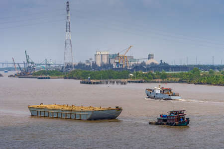 Long Tau River, Vietnam - March 12, 2019: Phuoc Khanh area. Large barge filled with sand is pulled by small green boat. In back, green foliage and cluster of industrial plants, under blue sky. Editöryel