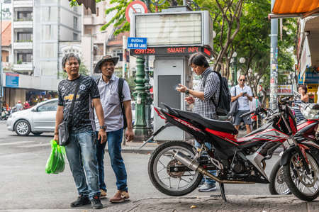 Ho Chi Minh City, Vietnam - March 12, 2019: Downtown. Young men and their phones and motorcycles in street scene with traffic, shops, buildings and street signs. Redakční