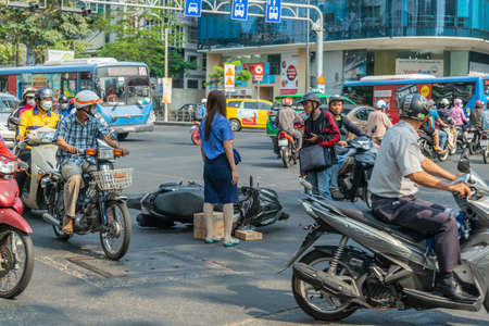 Ho Chi Minh City, Vietnam - March 12, 2019: Downtown street scenery Accident. Blue public bus cuts off scooter, on the ground. Bus has fled the scene. People come to see. Young woman addresses male victim. 新聞圖片