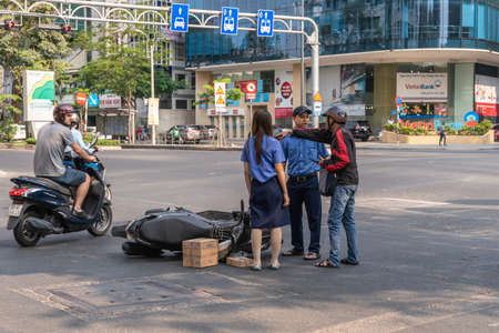 Ho Chi Minh City, Vietnam - March 12, 2019: Downtown street scenery Accident. Blue bus cuts off scooter, on the ground. Bus has fled the scene. Victim explains to police, Young woman confirms as witness.