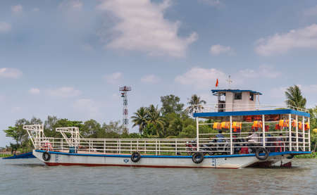 Tan Phong, Mekong Delta, Vietnam - March 13, 2019: Brownish Mekong river and a standard blue-white ferry boat transporting pedestrians and motorcycles. Backed by green belt under blue cloudscape. Safety vest add color.