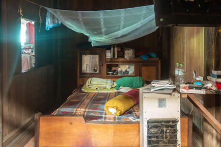 Cai Be, Mekong Deltal, Vietnam - March 13, 2019: Small bedroom with office table and white refrigerator. Azure Mosquito net above bed. Small window makes room rather dark.