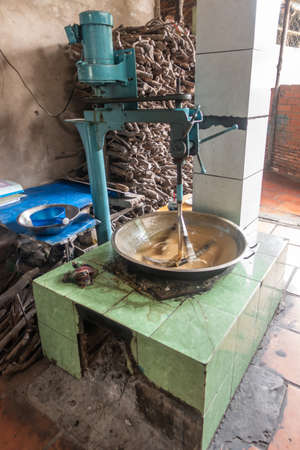 Blue machine stirs light brown candy dough in metal basin standing on green tiled rudimentary oven. Firewood in back.