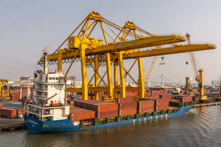 Ho Chi Minh City, Vietnam - March 13, 2019: Ben Nghe port on Song Sai Gon river at sunset. Blue Vietsun Pacific container vessel with maroon boxes and huge yellow cranes in front of container yard. Banque d'images - 134758287