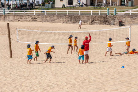 Newcastle, Australia - December 10, 2009: Lifesaver Trainee kids in orange garb play volleyball under guidance of instructor in red shirt on sandy beach. Boardwalk with people and buildings in back.