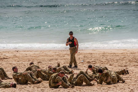 Newcastle, Australia - December 10, 2009: Group of camouflage clad young Australian Marines exercise stomach crunches on sandy beach at greenish water edge. Instructor present.