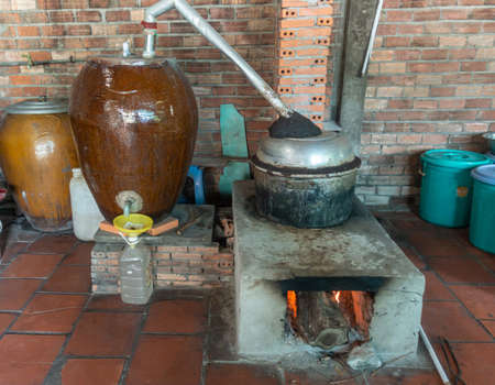 Cai Be, Mekong Deltal, Vietnam - March 13, 2019: Installation distilles fermented rice and honey by heating liquid to vaporize alcohol and not the water. Vapor condenses in brown vat and drips out at bottom in plastic bottle. Editorial