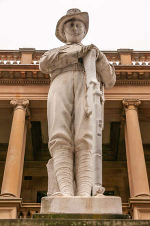 Newcastle, Australia - December 10, 2009: Closeup of white statue of soldier resting on rifle at WW1 35th infantry battalion memorial. Silver sky and beige classical building.