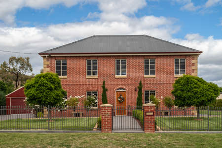 Richmond, Tasmania, Australia - December 13, 2009: Red brick stone two-story mansion in well maintained sober green garden with trees and white flowers under blue cloudscape. 報道画像