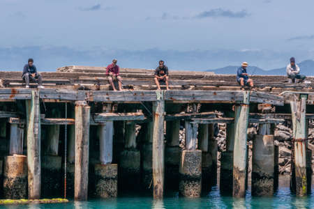 Stanley, Tasmania, Australia - December 15, 2009: Row of 5 men sitting on gray-brown wooden pier fishing in azure sea with rods under blue cloudscape.