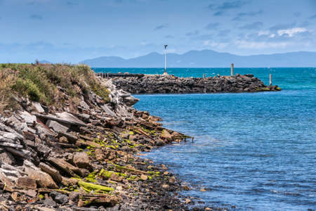 Stanley, Tasmania, Australia - December 15, 2009: Rocky coastline and breakwater of the port in blue seawater under blue cloudscape with dark hills on other side of bay. 스톡 콘텐츠