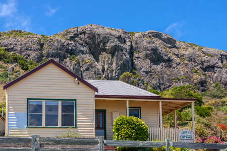 Stanley, Tasmania, Australia - December 15, 2009: The beige painted house called Abbeys Cottage is a B&B offering accommodations. Garden and cliff rocks in back under blue sky. Editorial