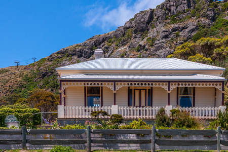 Stanley, Tasmania, Australia - December 15, 2009: The beige painted house called Abbeys Spa cottage houses a massage parlor and well being sanctuary. Garden and rock cliffs in back under blue sky.