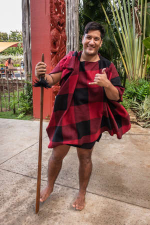 Laie, Oahu, Hawaii, USA. - January 09, 2020: Polynesian Cultural Center. Closeup of young male Maori warrior showing the Shaka sign. Black and red garb. Back is green vegetation and maroon totem sculptures.