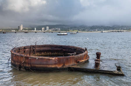 Oahu, Hawaii, USA. - January 10, 2020: Pearl Harbor. Rusty part of USS Arizona sticks out of gray sea water with Honolulu skyline in back under rainy cloudy sky.