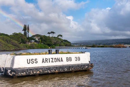 Oahu, Hawaii, USA. - January 10, 2020: Pearl Harbor. Historic white off-dock mooring point for USS Arizona on blueish water under blue cloudscape. Belt of foliage and rainbow.
