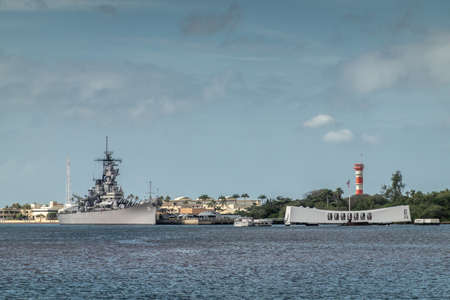Oahu, Hawaii, USA. - January 10, 2020: Pearl Harbor. Gray USS Missouri together with USS Arizona Memorial side by side on blueish water and under blue cloudscape. Airfield tower, Green foliage belt.