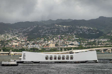 Oahu, Hawaii, USA. - January 10, 2020: Pearl Harbor. White USS Arizona Memorial and Ford Island bridge in back. Green Hills with white buildings under rainy dark cloudscape behind.