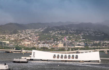Oahu, Hawaii, USA. - January 10, 2020: Pearl Harbor. White USS Arizona Memorial and Ford Island bridge in back. Green Hills with white buildings under rainy blue cloudscape behind.