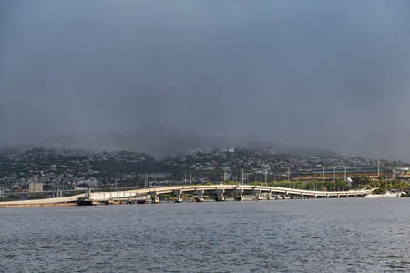 Oahu, Hawaii, USA. - January 10, 2020: Pearl Harbor. Ford Island bridge froms white line between gray water a belt of green hills with white houses. All under a dark foggy rain-filled sky.