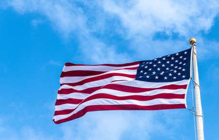Oahu, Hawaje, USA. - 10 stycznia 2020: Pearl Harbor. Zbliżenie latające amerykańską flagę przeciw błękitne niebo z niewielkimi białymi chmurami.