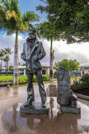 Oahu, Hawaii, USA. - January 10, 2020: Pearl Harbor. Wet Lone waiting sailor bronze statue under green foliage and blue cloudscape. Wet surface around and green lawn in back. Editorial