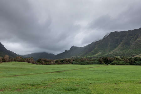 Kaaawa, Oahu, Hawaii, USA. - January 11, 2020: Kualoa valley shows deep green meadow with dirt road tearing a line and forested flanks of tall mountains on both sides under cloudy rainy sky.