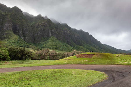 Kaaawa, Oahu, Hawaii, USA. - January 11, 2020: Dirt road makes U-turn ingreen meadow with dark brown to black high rocky cliffs on side of Kualoa valley under cloudy rainy sky.