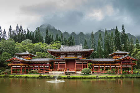 Kaneohe, Oahu, Hawaii, USA. - January 11, 2020: Maroon walls and gray roof, Byodo-In Buddhist temple with koi-pond in front, green trees and mountain range in back under dark rainy sky with white patches.