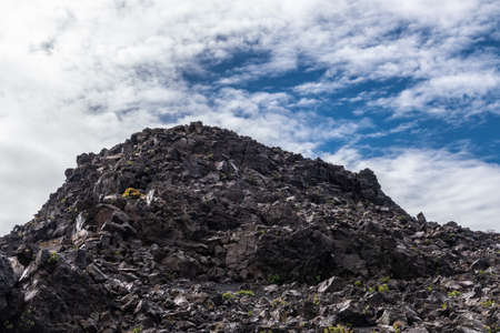 Haleakala Volcano, Maui, Hawaii, USA. - January 13, 2020: Mountain of black lava rocks at edge of the crater under white cloudscape with blue patches. Some small yellow vegetation.