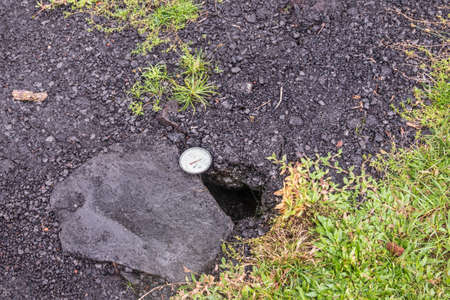 Leilani Estate, Hawaii, USA. - January 14, 2020: Devastation in parts untouched by 2018 lava. Dial placed in crack of road to measure temperature. Placed by government security forces.