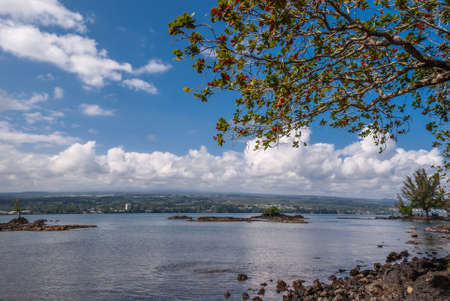 Hilo, Hawaii, USA. - January 9, 2012: Coastline with rocks and green trees of Liliuokalani Gardens. Blue sky with white cloudscape and blue ocean water. Look over ocean to opposite shore..