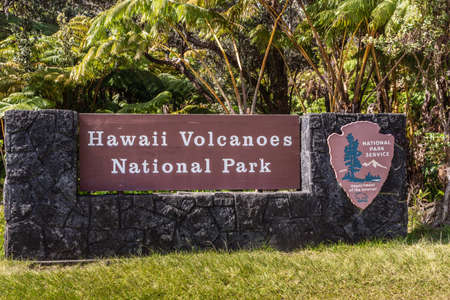 Kilauea volcano, Hawaii, USA. - January 9, 2012: White on brown sign of Hawaii Volcanoes National Park with green lawn in front and green tree vegetation in back. Foto de archivo