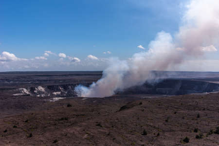 Kilauea volcano, Hawaii, USA. - January 9, 2012: View on full circle Kalemaumau crater producing white-brown long flume in black lava environement under blue sky with white clouds. Foto de archivo