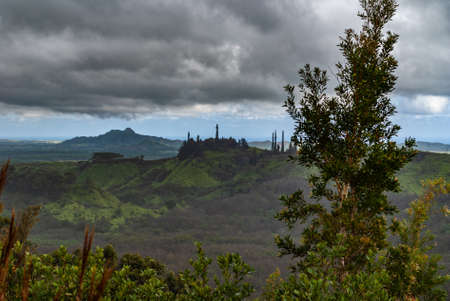 Kauai, Hawaii, USA. - January 11, 2012: Dark rainy cloudscape with blue at the horizon over green, wild, hilly hinterland. Green tree foliage up front. Banco de Imagens