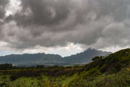 Kauai, Hawaii, USA. - January 11, 2012: Dark rainy cloudscape with light blue at the horizon over green, wild, hilly hinterland. Mountains with dark shadows in back.