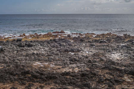 Kauai, Hawaii, USA. - January 11, 2012: Black lava rocks at Kawailoa beach in front of azure and gray ocean under light blue sky with far away clouds.