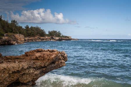 Kauai, Hawaii, USA. - January 11, 2012: Brown rough rocky coastline at Kawailoa bay with blue ocean, blue sky and white clouds. Green trees on top of cliffs. Hidden fisherman.