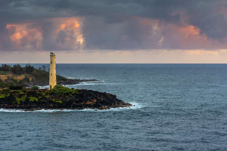 Nawiliwili, Kauai, Hawaii, USA. - January 11, 2012: Yellow Ninini lighthouse on blue ocean-shore rocks early morning. sunsrise sets cloudscape on fire. Some green foliage on land.
