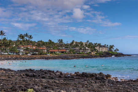 Poipu, Kauai, Hawaii, USA. - January 11, 2012: Black rocks form Brenneckes beash and bay with blue ocean water in front of Poipu shores with large mansions, green trees, under blue cloudscape.