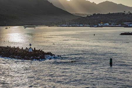 Nawiliwili, Kauai, Hawaii, USA. - January 11, 2012: Evening light on the inner harbor with plenty of small boats. Sunrays and light reflecting on water with breakwater. Black mountains shielding sky.