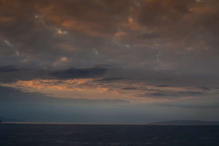 Lahaina, Maui, Hawaii, USA. - January 12 2012: Early morning light over ocean with fog near west side of the island, produces a dark cloudscape with parts as if set on fire.